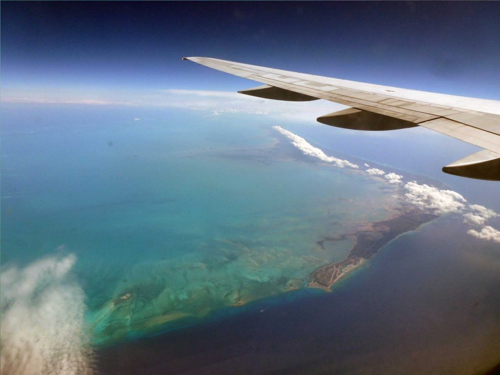 Airplane wing over ocean and island